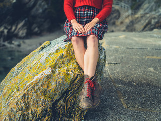 Young woman relaxing on rock at the coast