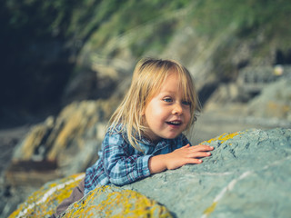 Little toddler hiding behind rock on the coast
