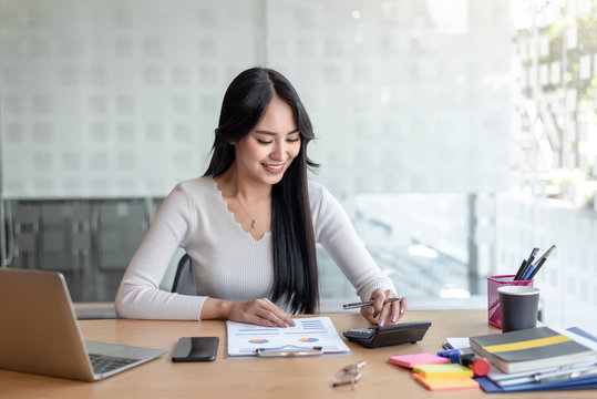 Business women using calculator at working with financial report.