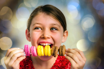 beautiful girl eating a skewer of colorful macaroons