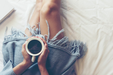 Close up legs women on white bed in the bedroom. Women reading book and drinking coffee in morning relax mood in winter season. Lifestyle Concept.