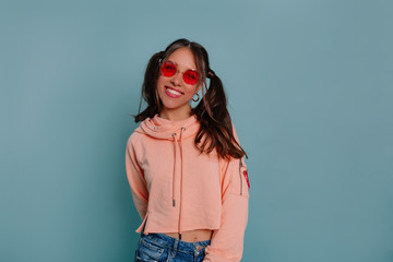 European smiling young woman in funny round glasses laughing to camera over isolated background