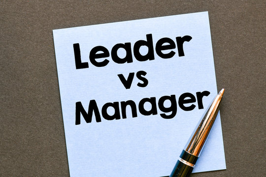 Leader vs Manager text on small sheet and wooden background. High resolution photo - business concept