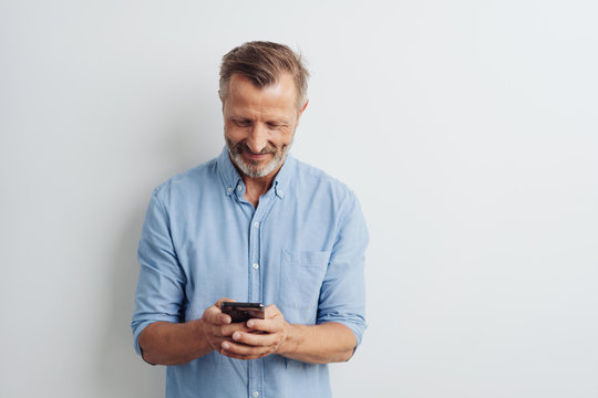 Smiling middle-aged man texting a message