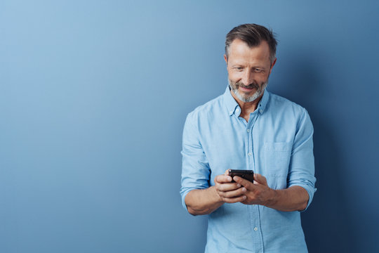 Middle-aged man reading an sms on his mobile