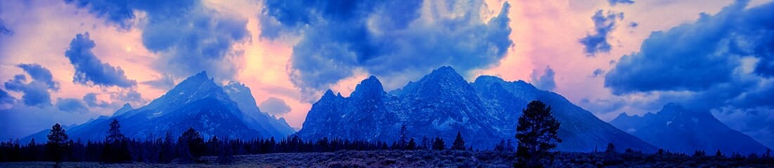 Panorama of a mesmerizing mountainous scenery under the cloudy sky with warm colors