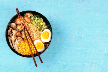 Ramen. Soba noodles with eggs, shiitake mushrooms, and vegetables, overhead shot on a blue background with chopsticks and copyspace