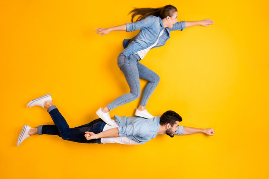 Top view above high angle flat lay flatlay lie full length body size view concept of his he her she beautiful handsome spouse flying isolated on bright vivid shine vibrant yellow color background