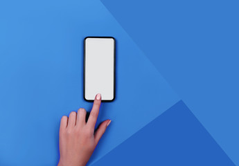 Top view of a woman hand using phone on Classic Blue color of the year 2020 background