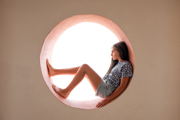 Young barefoot girl curled inside a round opening