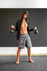 Muscular man in hoodie working out with weights