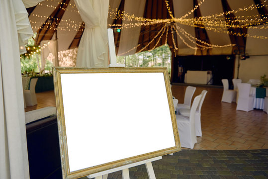 Wood easel with blank white board at wedding reception in restaurant, copy space for text. Table list or seating chart at wedding banquet