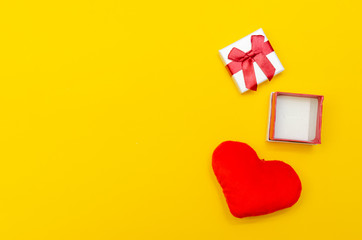 Empty open ring box and heart on yellow background. concept of the holiday, Valentine's Day
