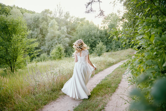 Portrait of beautiful bride in long white wedding dress walking in garden at sunset, back view. Wedding concept, copy space