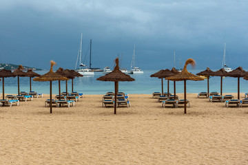 wide sandy beach with sun loungers and straw umbrellas on the background of the blue sea and white yachts in the Spanish resort of Magaluf