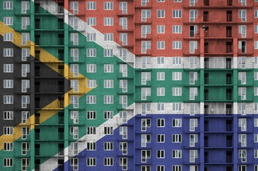 South Africa flag depicted in paint colors on multi-storey residental building under construction. Textured banner on brick wall background