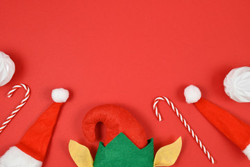 Seasonal flat lay with Christmas elf hat and ears, tree baubles, santa hats and candy canes on empty copy space on red background at top