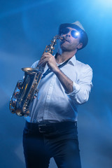 Man playing sax in cold blue laserlight