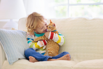 Child playing with cat. Kid and kitten.