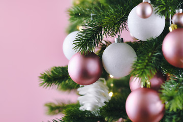 Close up of decorated Christmas tree with white seasonal and pink tree ornaments like baubles and stars on pink background with lights in background