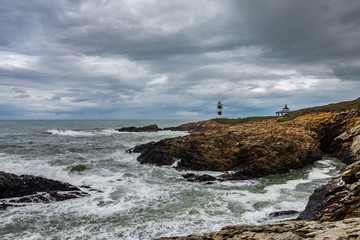 Lighthouse with cloudy stormy sky and rough coastline