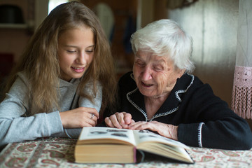 Grandmother with a little girl - granddaughter reading a book.