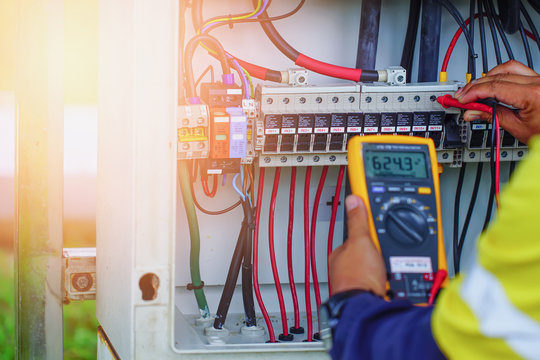 Workers use Multimeter to measure the voltage of electrical wires produced from solar energy for confirm to systems working normal