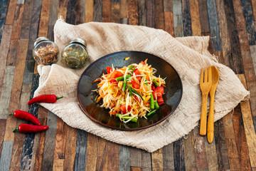 Traditional Thai food papaya salad prepared with fine slices of papaya, tomatoes, green beans and peanuts.
