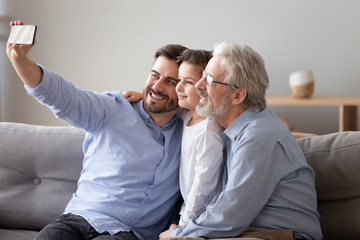 Three generations relatives men sitting on couch take selfie photo