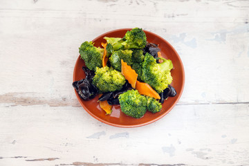 Mixture of vegetables cooked with broccoli and black mushrooms served in a plate for eating