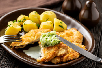 Chop pork cutlets , served with boiled potatoes and tzatziki dip.