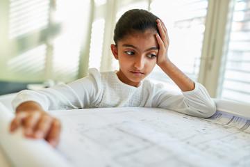 Kind als Architekt schaut nachdenklich auf Zeichnung