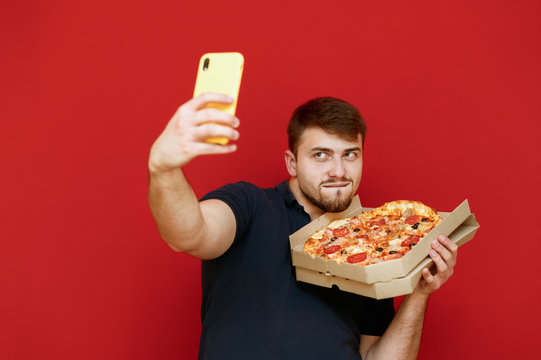 Funny bearded man taking selfie with pizza box on red background, looking at smartphone and making funny face. Cheerful man taking photo with pizza delivery box. Isolated.