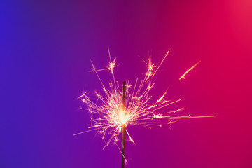 A burning sparkler in bright neon background. Concept of new year party or celebration: a bengal fire in vivid neon lights