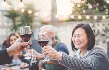 Happy family eating and drinking red wine at dinner barbecue party outdoor - Mature and young people dining together on terrace - Youth and elderly weekends lifestyle activities and food concept