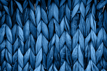 Rustic natural wicker texture toned in classic blue monochrome color. Braided pattern macro photography.