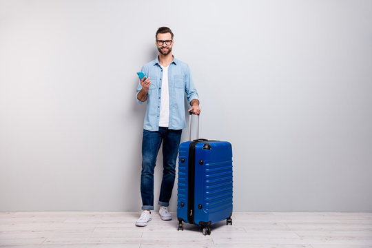 Full length photo of handsome hipster guy holding telephone big tourist bag have student visa europe traveler wear specs denim outfit isolated grey color background