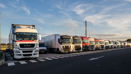 Row of trucks on a truck parking along the E17 highway in Belgium on June 23, 2017