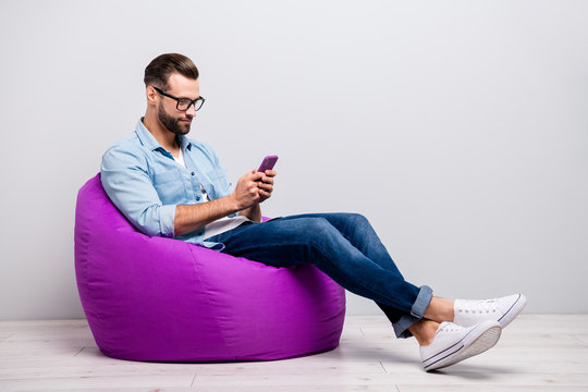 Full size profile photo of crazy guy sitting comfy soft violet armchair holding telephone chatting colleagues wear specs casual denim outfit isolated grey color background