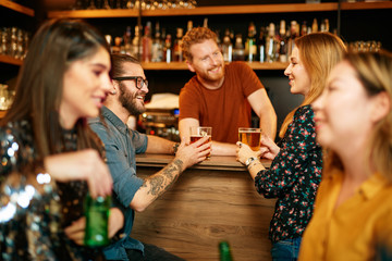 Small group of multi cultural friends standing in pub, leaning on bar counter, chatting and holding pints of beer. In foreground are girls. Focus on couple near bar counter.