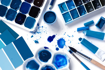 Art supplies and classic blue colors in the white textured paper