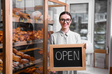 Female business owner holding OPEN sign in bakery