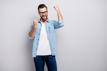 Photo of attractive crazy business guy celebrating successful startup investment yelling raising fists wear specs casual denim outfit isolated grey color background