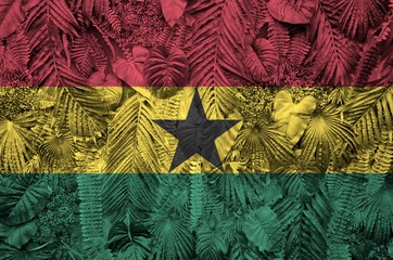 Ghana flag depicted on many leafs of monstera palm trees. Trendy fashionable backdrop