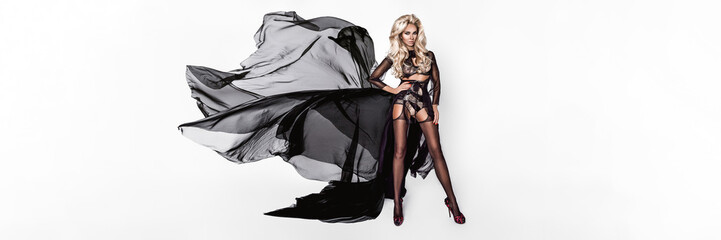Fashion woman in fluttering black dress. Sexy lingerie model. White background. - Image