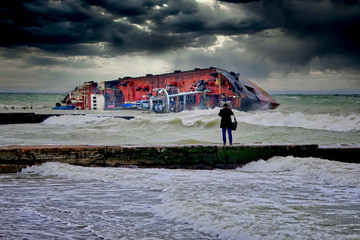 Photo sur Aluminium Taupe After a severe storm, the tanker was shipwrecked on the popular beach of Odessa, Ukraine. The ship lies on its side directly on the breakwater. Close-up dramatic photo.