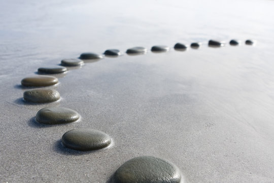 concept shallow depth of field black  stepping stones pebbles in shallow water way to success