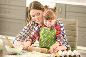 Happy mother and daughter cooking pastry at home