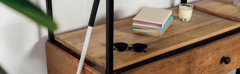 Fototapeta Panoramic shot of walking stick beside sunglasses and books on cupboard shelf obraz