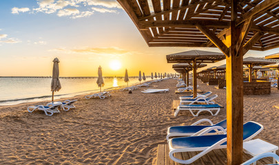 Wall Mural - Landscape with sunbeds and umbrella on the Red Sea beach at sunrise in Hurghada, Egypt